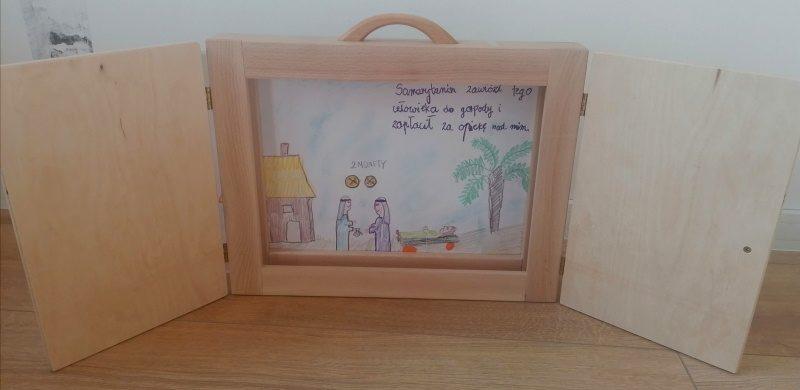 Na zdjęciu scena z teatrzyku o Samarytaninie. Jeden z obrazków w drewnianej skrzynce.