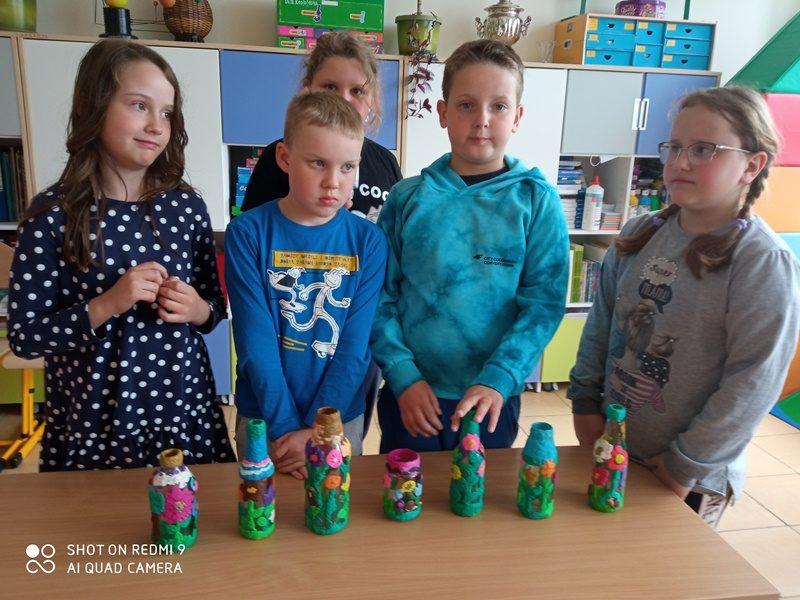 Klasa szkolna. Pośrodku przy stole 5 uczniów. Na stole prace uczniów: pomalowane i wyklejane butelki i słoiki.