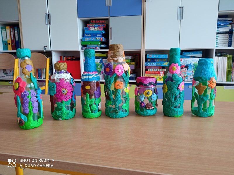 Klasa szkolna. Na stole stoją prace uczniów: pomalowane i wyklejane butelki i słoiki.