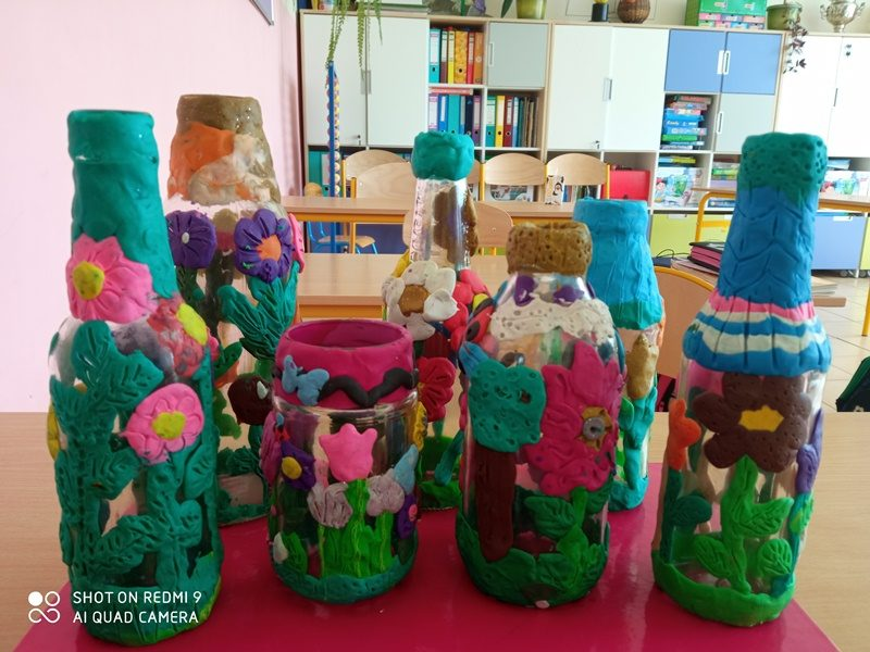 Klasa szkolna. Na stole prace uczniów: kolorowe wyklejanki na butelkach i słoikach.