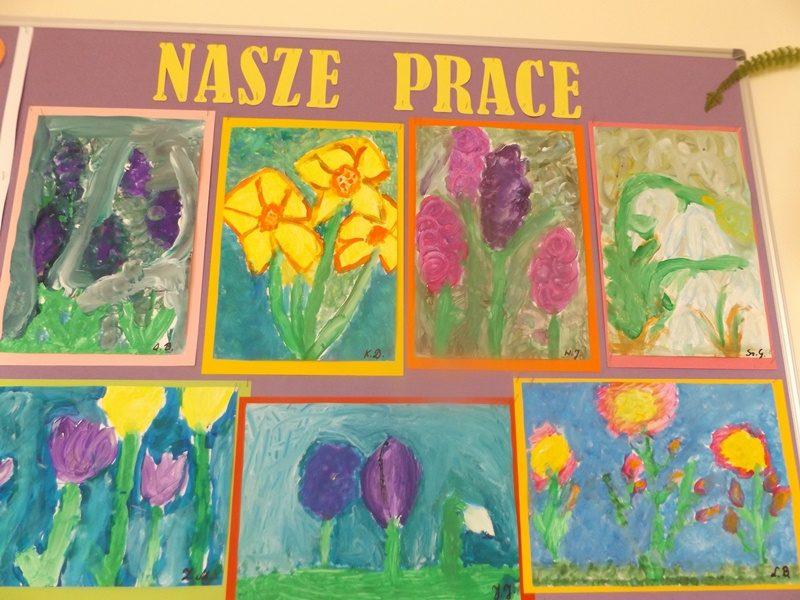 Gazetka szkolna na korytarzu. Tytuł gazetki: Nasze Prace. Na gazetce umieszczono 7 prac uczniów. Prace przedstawiają wiosenne kwiaty.