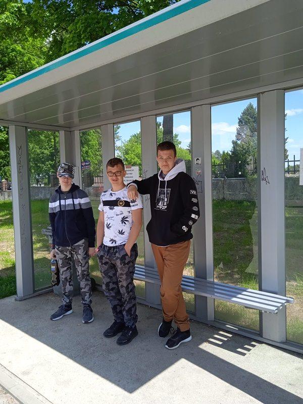 Przystanek autobusowy. Na przystanku stoi trzech uczniów.