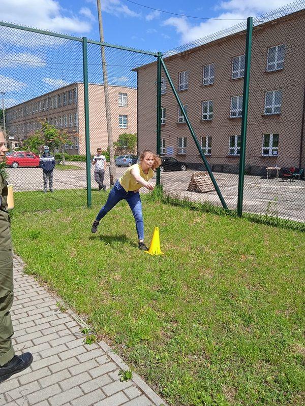 Boisko szkolne. Uczennica bierze udział w konkurencji rzucania do celu.