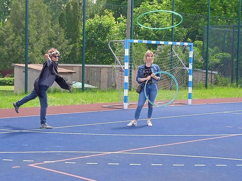 Boisko szkolne. Dwie nauczycielki. Jedna z nich rzuca hula hop.