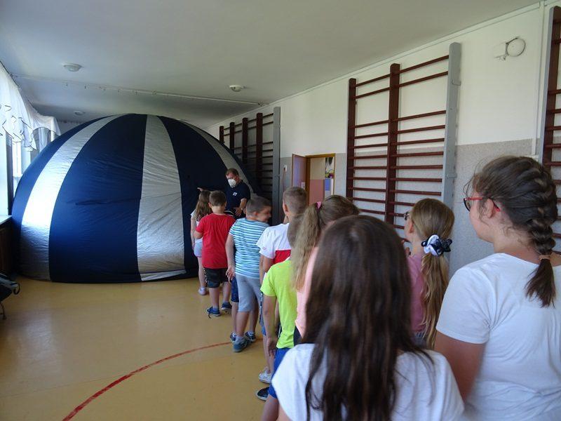 Korytarz szkolny. W głębi ustawione oceanarium. Uczniowie stoją do niego w kolejce.
