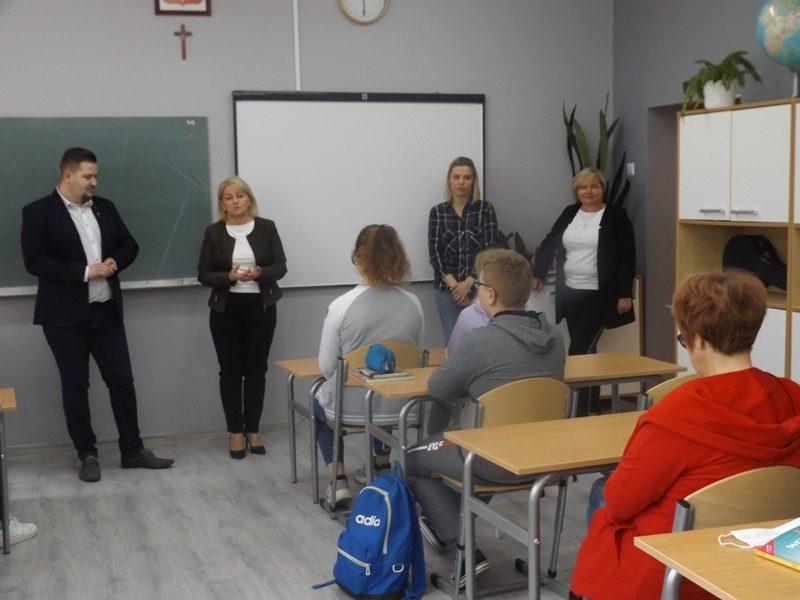 Sala szkolna. Przy tablicy przedstawiciele Urzędu Miejskiego w Olecku, w ławkach uczniowie.