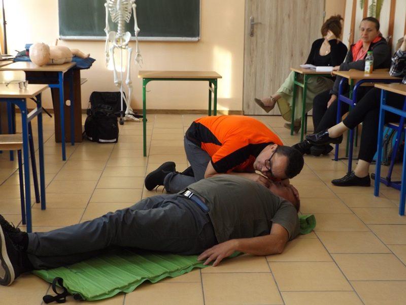 Klasa szkolna. Prowadzący szkolenie demonstruje praktycznie udzielanie pierwszej przedmedycznej.