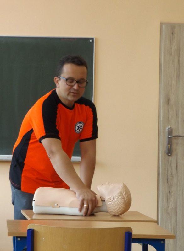 Klasa szkolna. Prowadzący szkolenie demonstruje udzielanie pierwszej pomocy za pomocą fantoma.