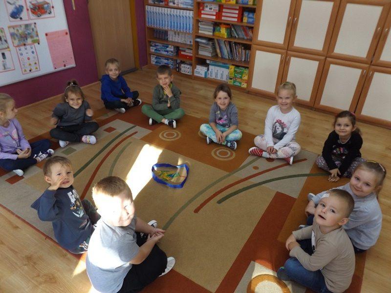 Sala przedszkolna. Na dywanie pośrodku sali siedzą w kółku dzieci.
