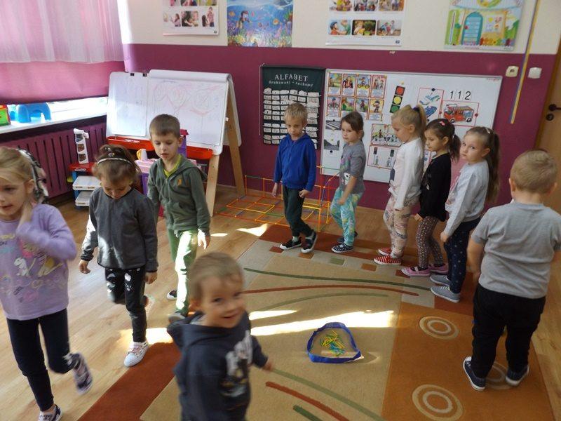 Sala przedszkolna. Pośrodku sali dzieci chodzą w kółko gęsiego, jedno za drugim.