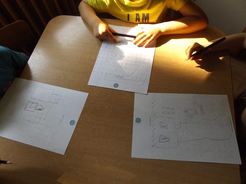 Sala przedszkolna. Przy stoliku siedzi trójka dzieci i wykonuje rysunki.