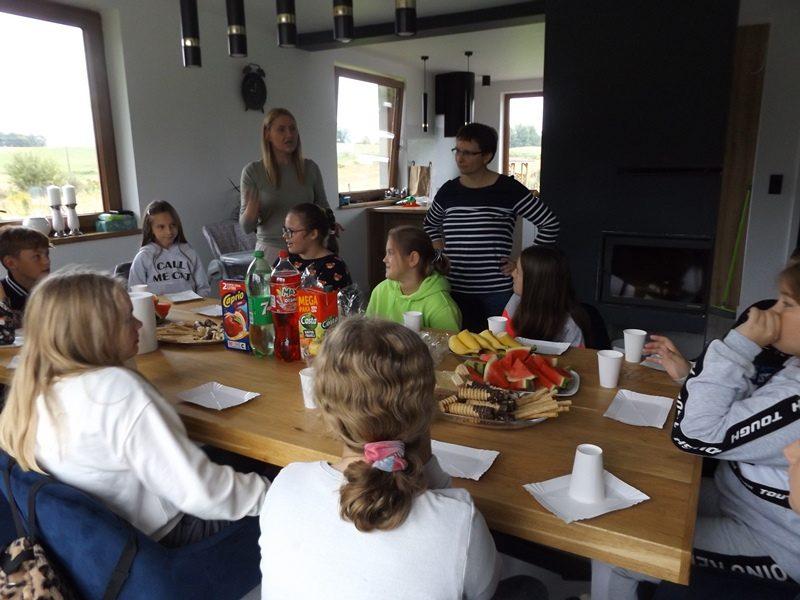 W domu. Poczęstunek. Uczniowie siedzą przy stole.  Na drugim planie stoja dwie wychowawczynie.