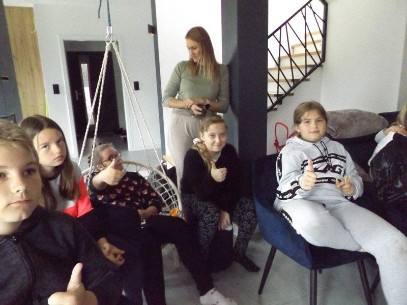 W domu. Uczniowie siedzą na krzesłach i ogladają film.