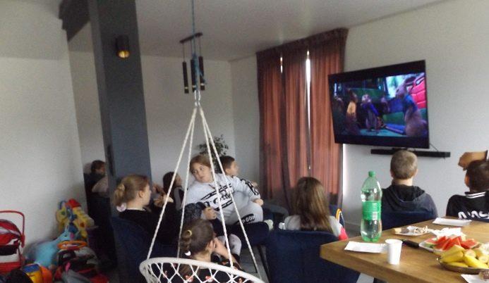 W domu. Uczniowie przed monitorem. Oglądają film.