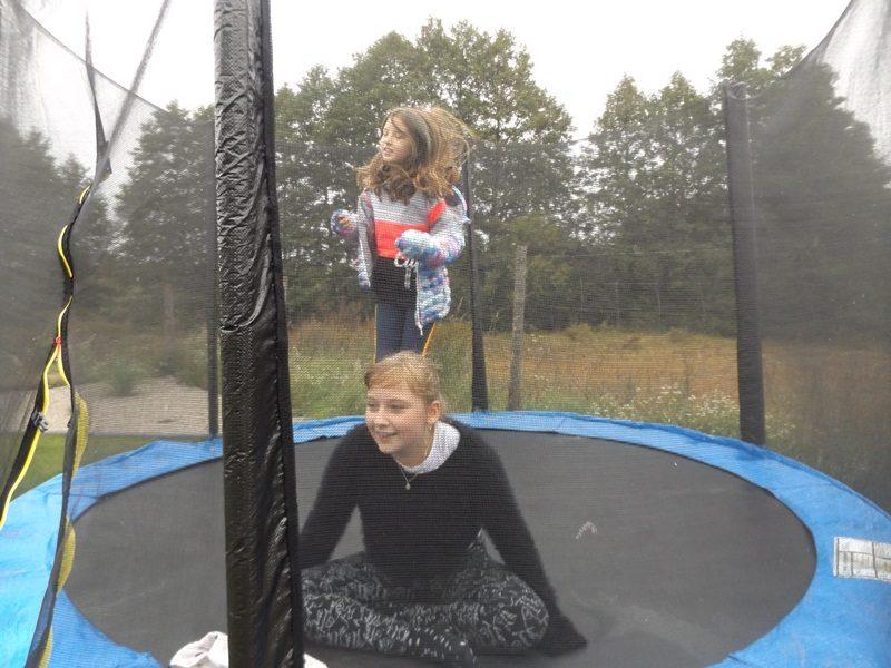 Dwie uczennice na trampolinie. Jedna siedzi, druga skacze.