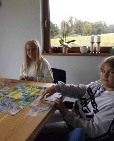 W domu. Dwie uczennice przy stole. Grają w grę planszową.