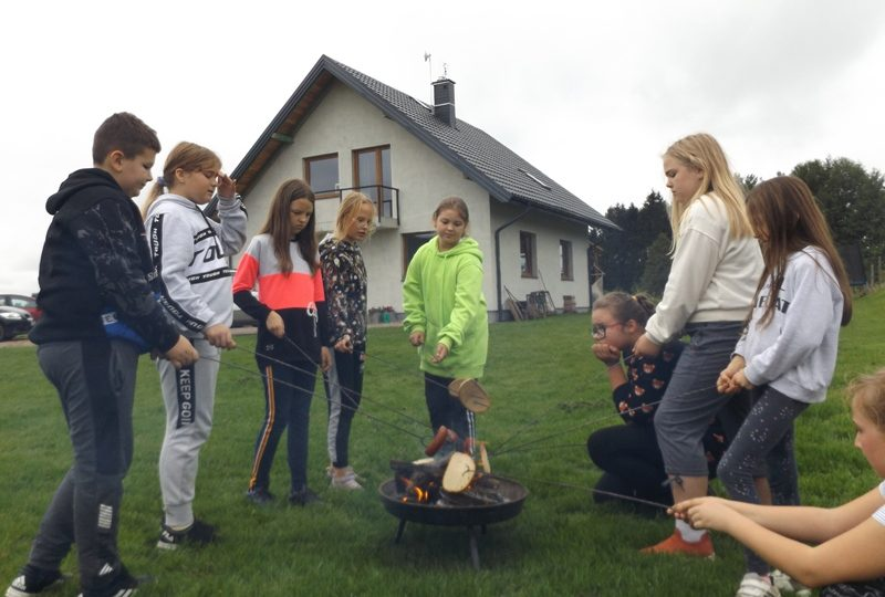 Przed domem. Uczniowie stoją wokół ogniska i pieką kiełbaski.