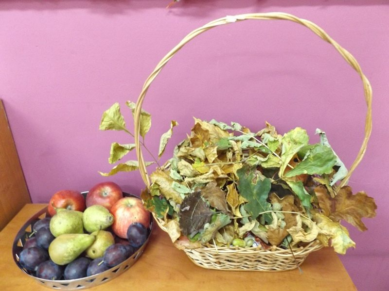 Na stole przy ścianie na stole stoi kosz wiklinowy z kolorowymi liśćmi. Obok kosza po lewej stronie stoi mniejszy koszyk z owocami.