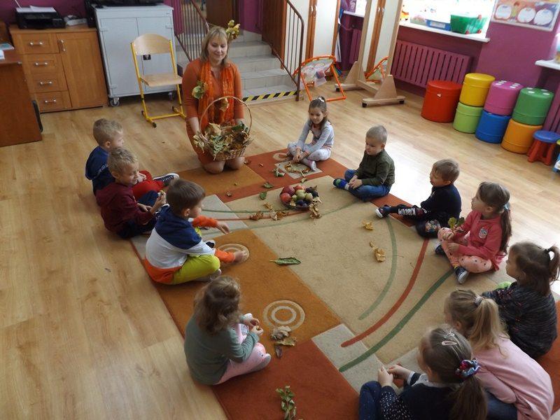 Sala przedszkolna. Pośrodku sali na dywanie siedza dzieci i wychowawczyni, która trzyma kosz z kolorowymi liśćmi.