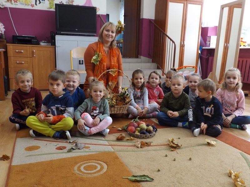 Sala przedszkolna. Na dywanie siedza dzieci. Przed dziećmi stoi koszyk z owocami i na dywanie leżą liście. Za dziećmi siedzi wychowawczyni z koszem liści.