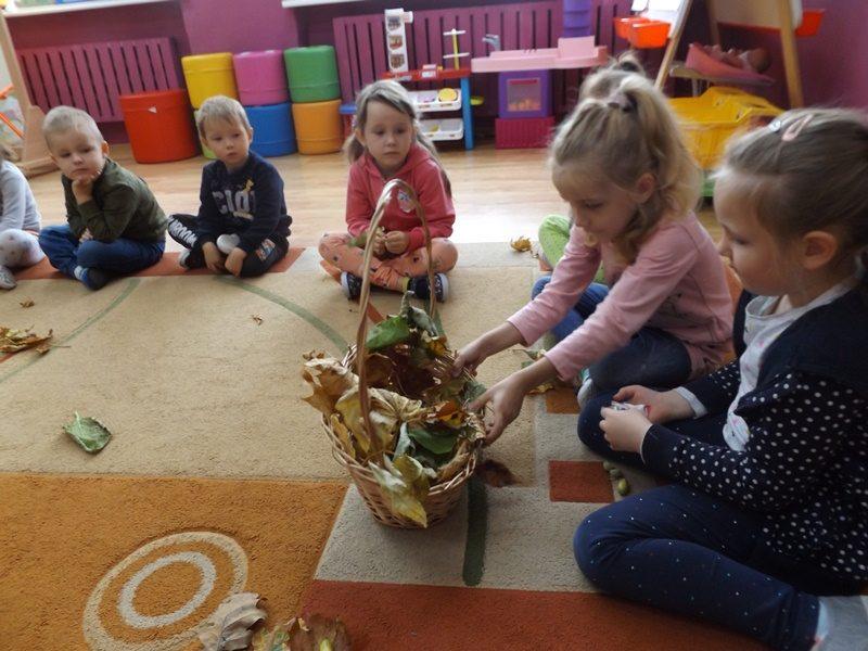 Sala przedszkolna. Na dywanie siedzą dzieci. Dziewczynka wybiera z kosza liście.