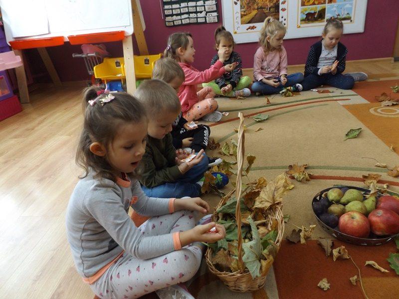 Sala przedszkolna. Na dywanie siedzą dzieci i bawią się liśćmi. Na dywanie stoi również kosz z owocami.