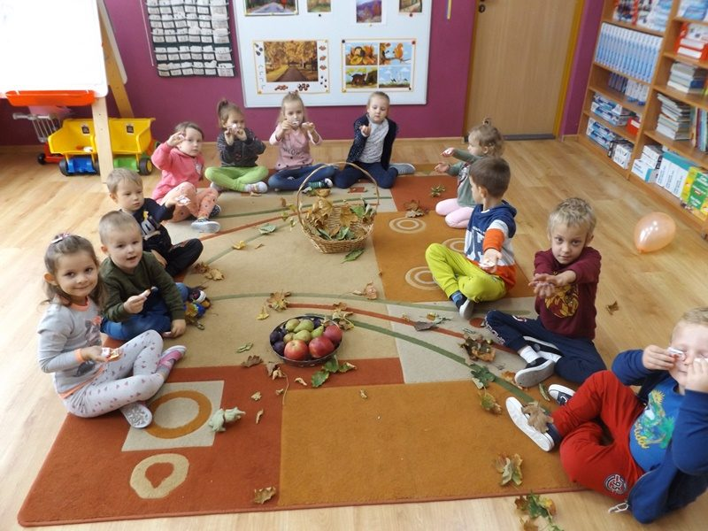 Sala przedszkolna. Na dywanie siedzą dzieci i bawia się liśćmi. Pośrodku dywanu stoi kosz z liśćmi i koszyk z owocami.