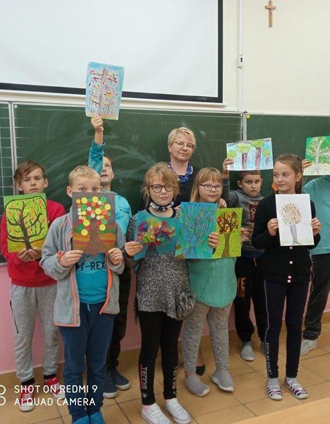 Klasa szkolna. Przy tablicy stoją uczniowie  i trzymają w ręce prace konkursowe.
