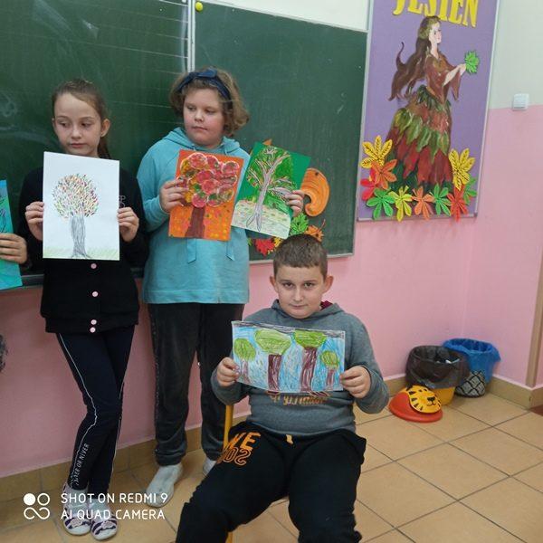 Klasa szkolna. Przy tablicy stoja dwie uczennice i trzymają w rękach prace konkursowe. Przy nich na krześle siedzi uczeń i prezentuje swoją pracę.