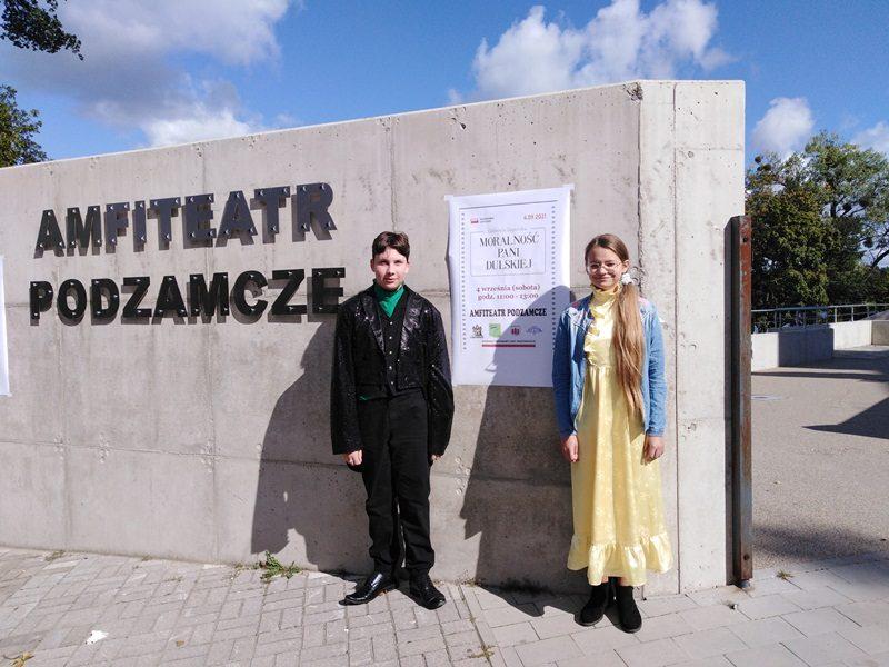 Ściana z napisem: Amfiteatr Podzamcze. Przy ścianie pod napisem stoją uczniowie szkoły, biorący udział w Narodowym czytaniu - Wojciech i Zuzanna.