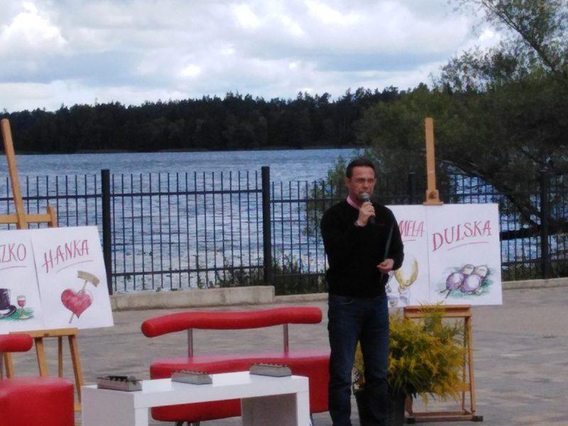 W tle Jezioro Oleckie Wielkie. Pośrodku zdjęcia w amfiteatrze stoi burmistrz Olecka i przemawia do zgromadzonych osób.
