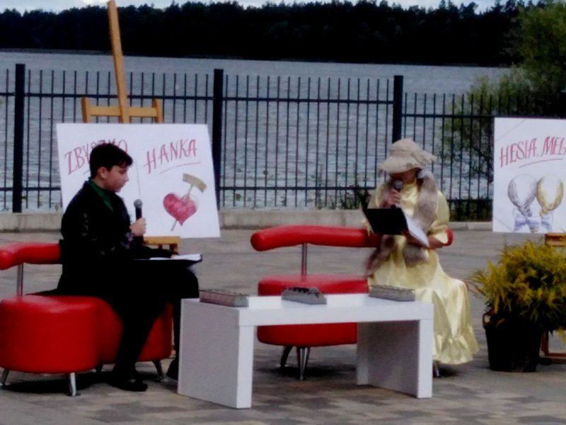 W tle Jezioro Oleckie Wielkie. Przy stoliku w amfiteatrze na fotelach siedzą uczniowie szkoły: Wojciech i Zuzanna, którzy czytają fragmenty utworu Moralność Pani Dulskiej.