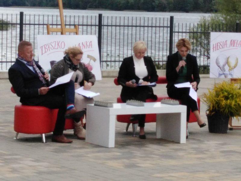 W tle Jezioro Oleckie Wielkie. Pośrodku, w amfiteatrze siedzą przy stoliku cztery osoby, czytający fragmenty utworu. Wśród czytających znajduje się dyrektor  szkoły, Beata Prześniak