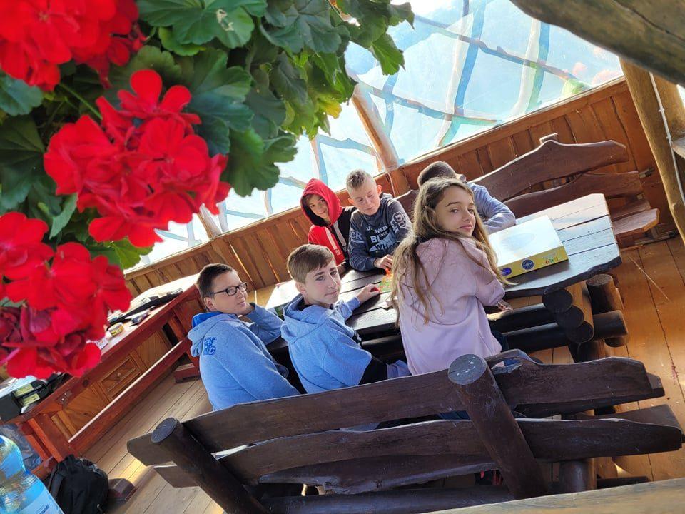 Wiata. Przy stole siedzą uczniowie i grają w gry planszowe.