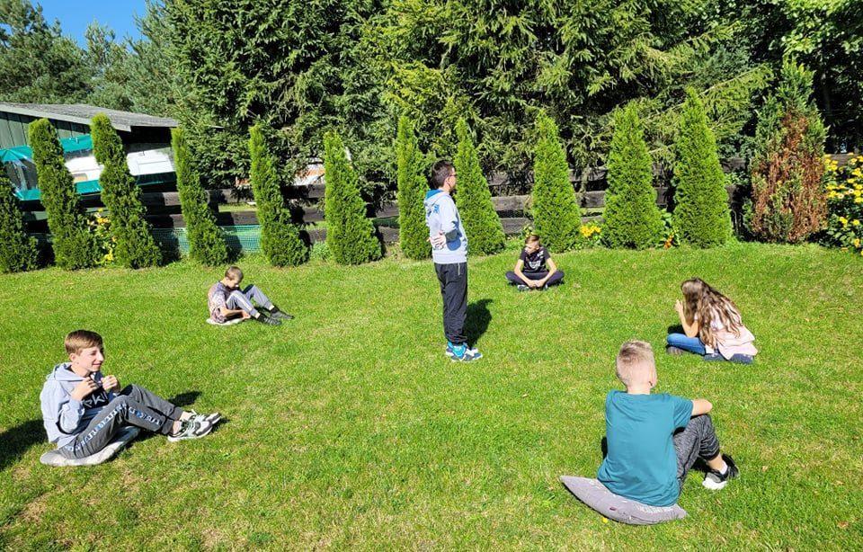 Na trawniku. Uczniowie siedzą w szerokim kole. Pośrodku koła stoi jeden z uczniów i wydaje polecenia zgodnie z regułami gry.