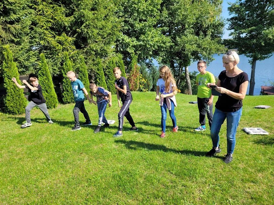 Na drugim planie jezioro. Na pierwszym uczniowie i wychowawczyni na trawniku. Uczniowie przygotowują się do biegu na czas.
