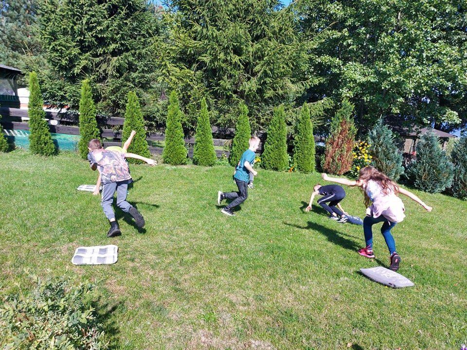 Na trawniku uczniowie podczas gry w zmianę miejsc.
