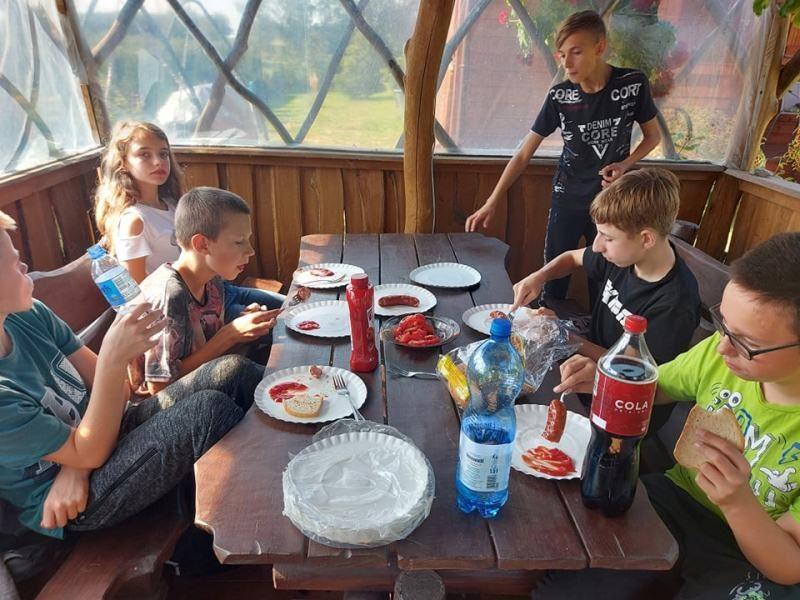 Wiata. Przy stole siedzą uczniowie i jedza kiełbaski z grilla.