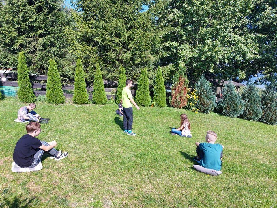 Uczniowie na trawniku podczas zabawy terenowej.