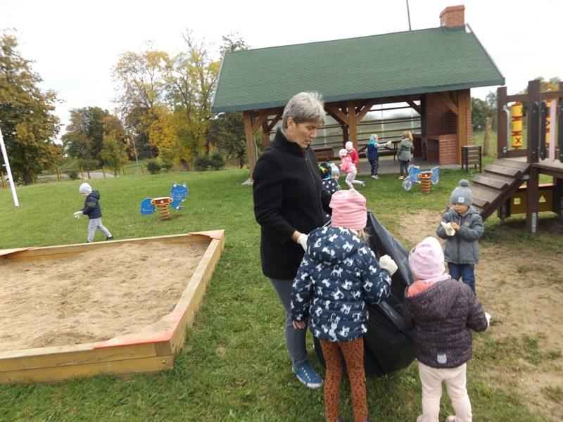 Dzieci sprzątaja plac zabaw.