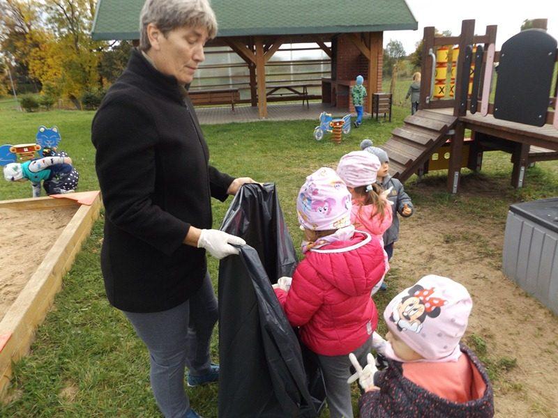 dzieci sprzątają plac zabaw i wrzucają śmieci do worka.