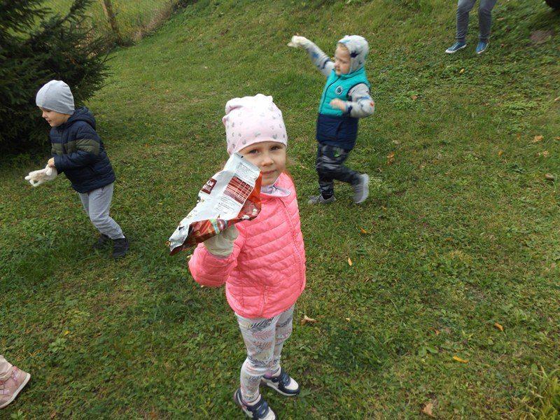 Teren posesji szkolnej. Dzieci sprzątają teren za wiatą. Dziewczynka trzyma w ręku papierowe opakowanie.