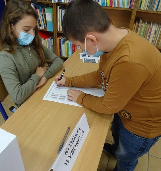 W lokalu wyborczym. Przy stole członek komisji wyborczej i wyborca, który podpisuje odbiór kart do głosowania.