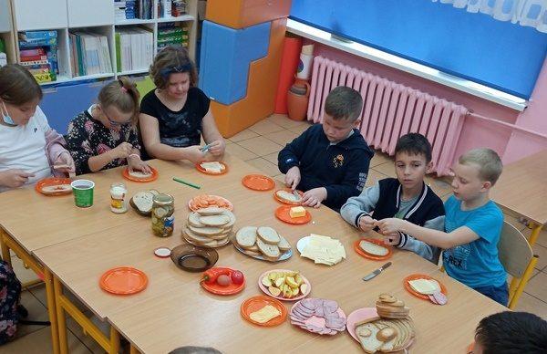 klasa szkolna. Uczniowie siedza przy stole i przygotowują kanapki.