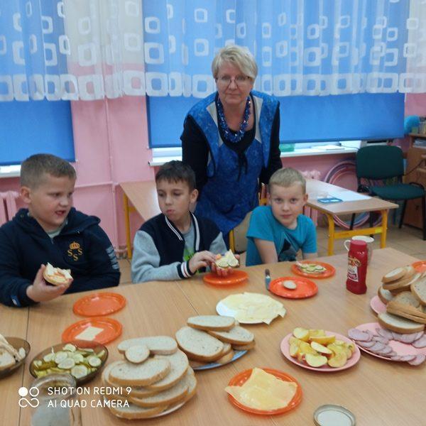 Klasa szkolna. Przy stole siedzi trzech uczniów i je kanapki. Za nimi stoi nauczycielka. Na stole na talerzach leżą kanapki i warzywa.