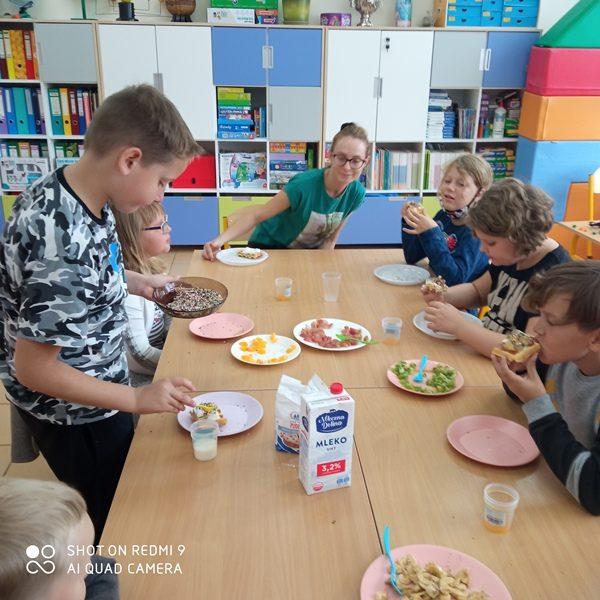 Sala szkolna.  Przy stole siedza uczniowie i praktykantka i jedzą kanapki oraz gofry.