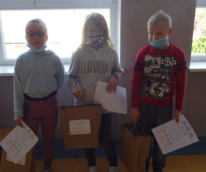 Korytarz szkolny. Przy oknie stoją zwycięzcy konkursu - trzy osoby. W rękach trzymają dyplomy i nagrody.
