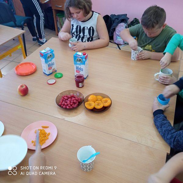 Sala szkolna. Uczniowie siedzą przy stole i przygotowują deser.