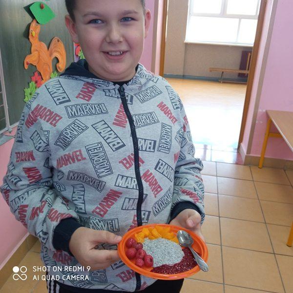 Sala szkolna. Uczeń prezentuje na talerzu przygotowany deser.