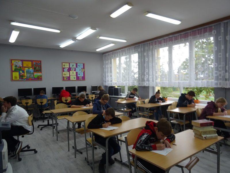 Klasa szkolna. Uczniowie siedzą przy stolikach i rozwiązują zadania.